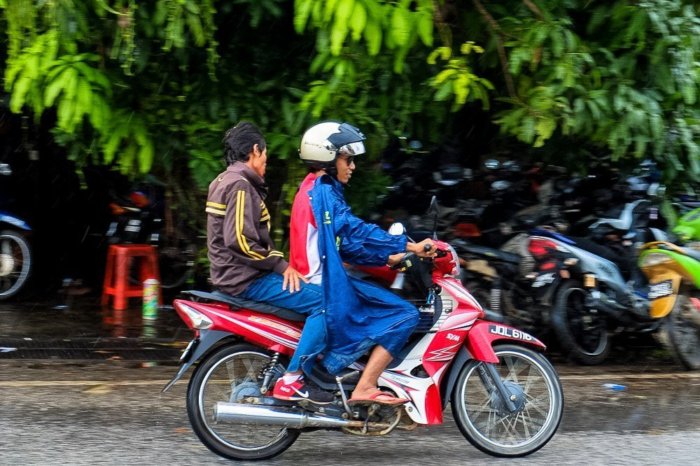 Man riding a motorbike wearing a rain jacket