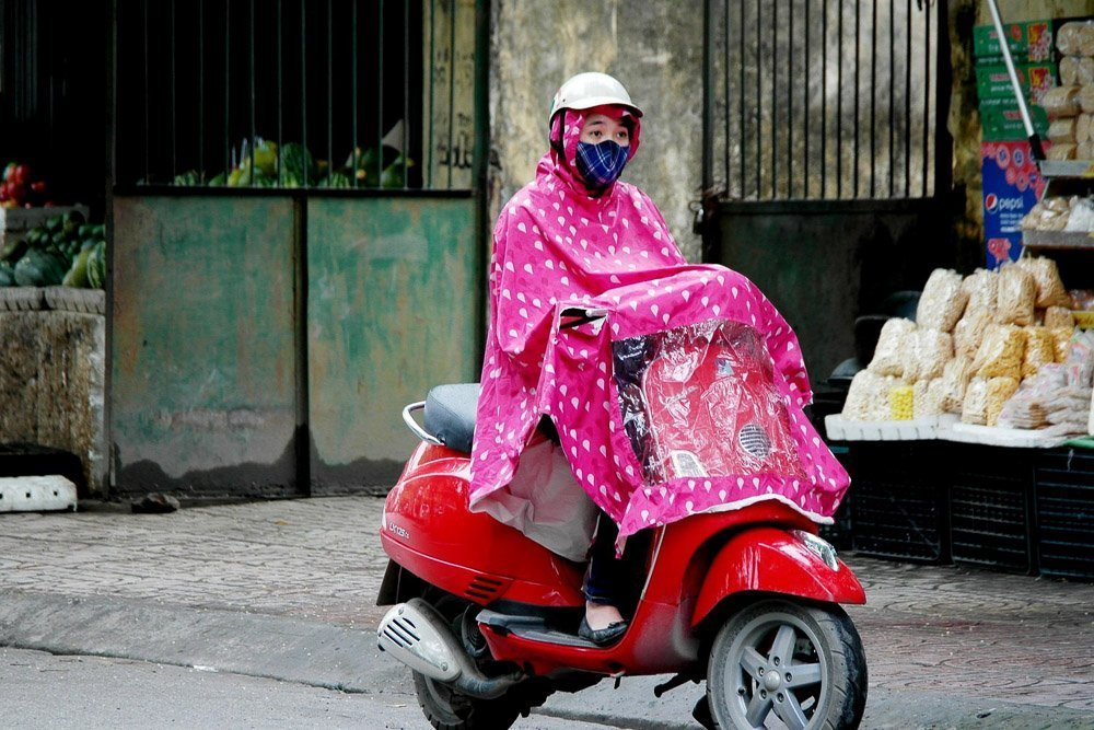 Woman on a scooter wearing a rain poncho