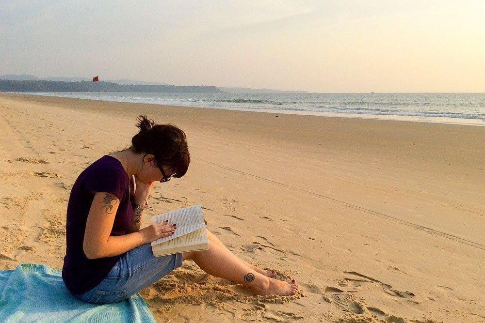 Sitting on the beach reading a book