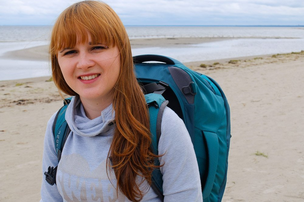 Una wearing her Osprey Fairview 40 backpack on the beach