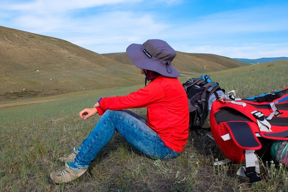 Una sitting on the ground after hiking - Best Cheap Travel Backpacks