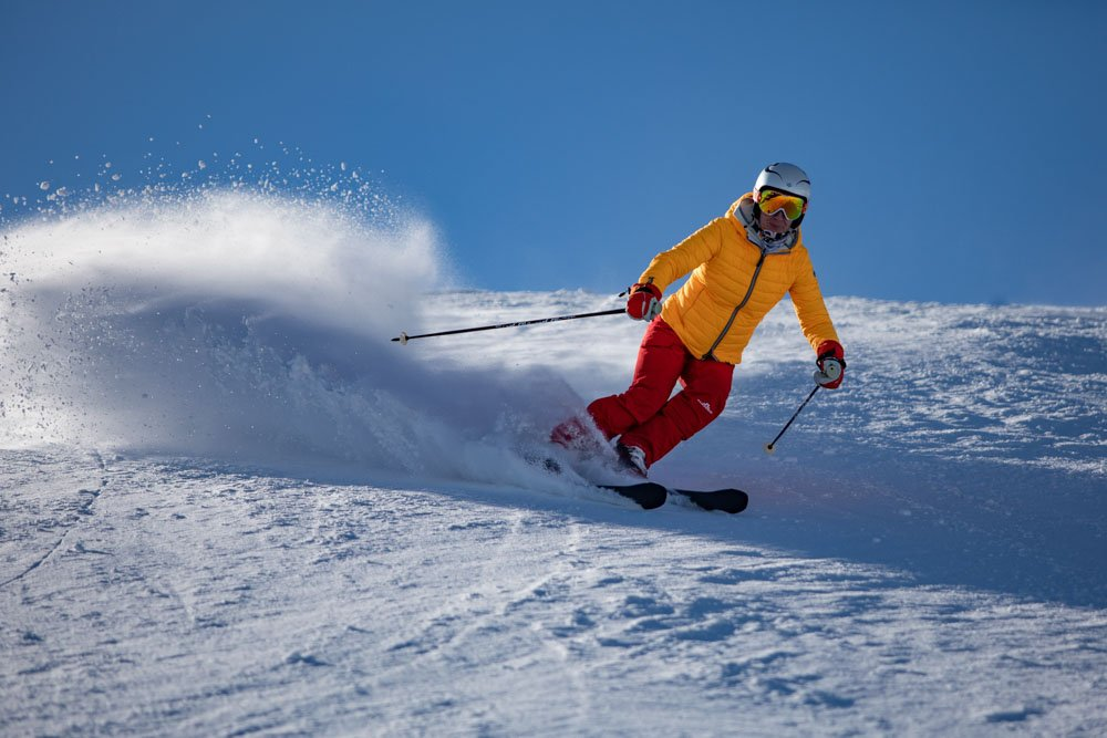 A person in yellow jacket skiing_