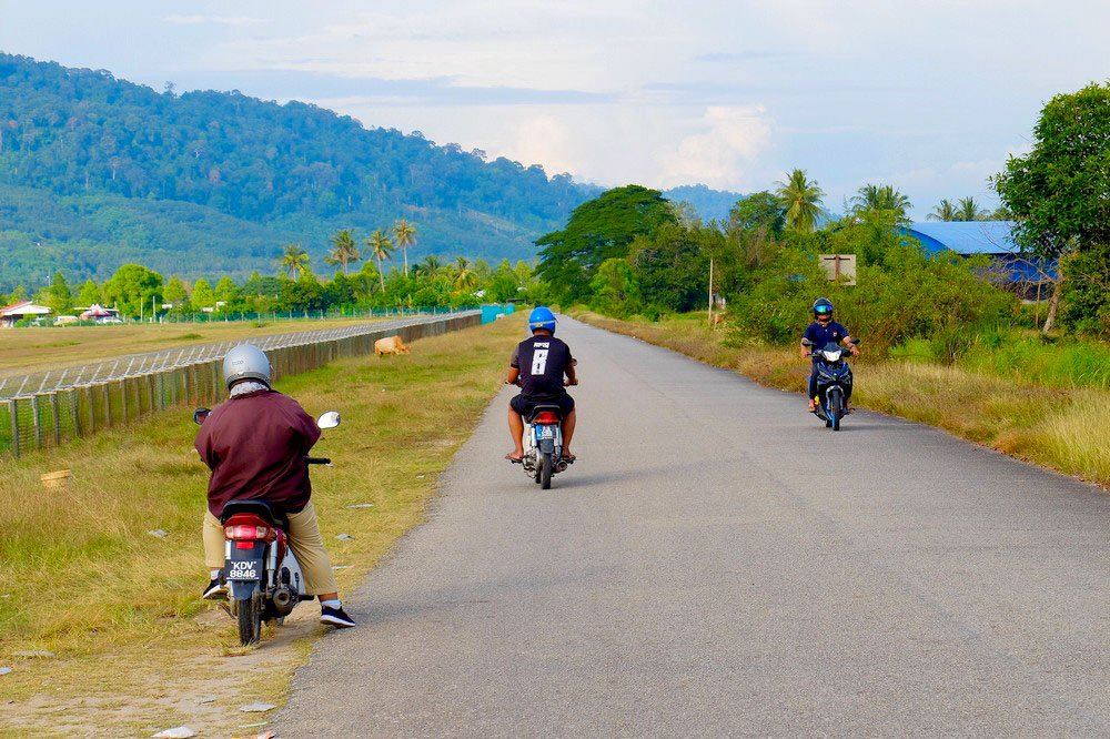 Men on scooters in Langkawi Malaysia