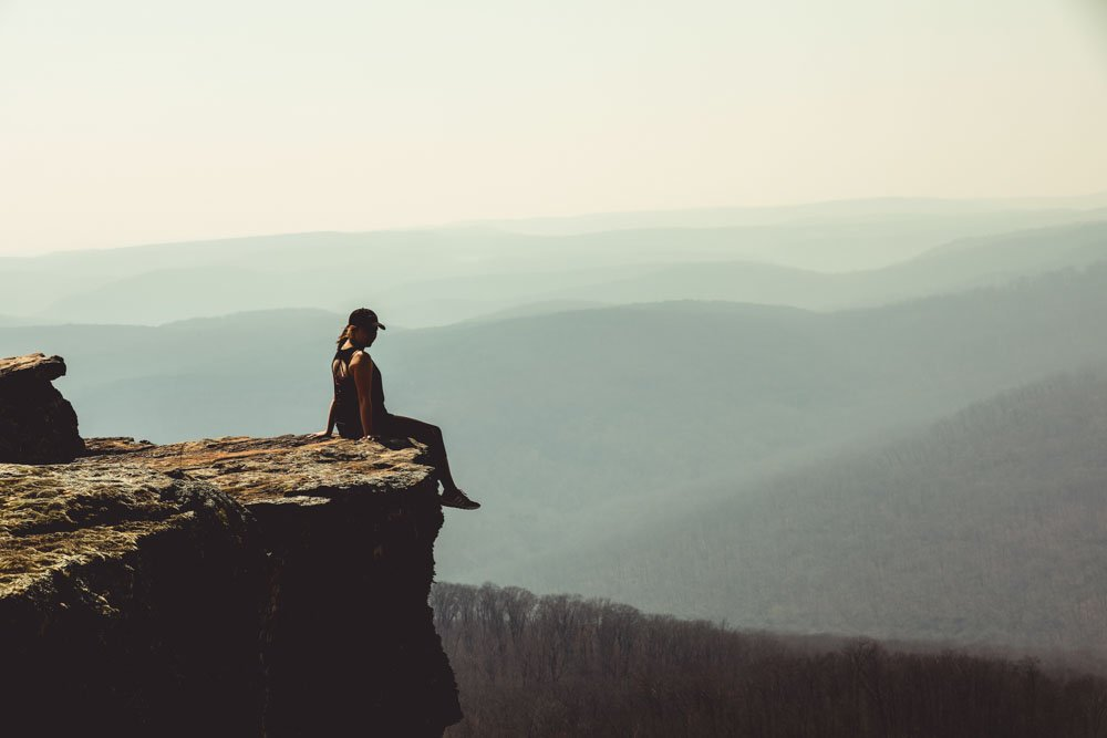 Woman sitting on the edge of a rock