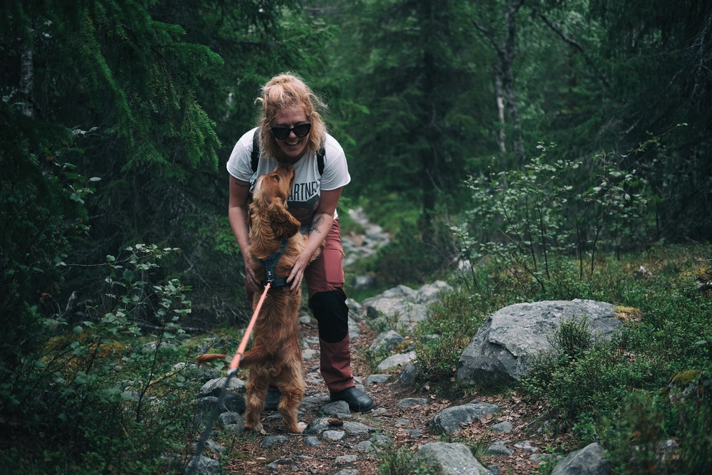 Woman hiking with a dog on a leash