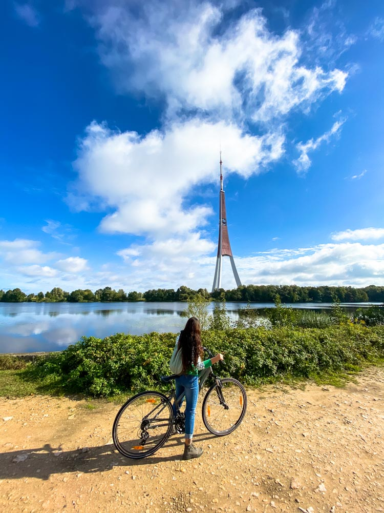 Standing with a bicycle with a Riga TV tower in background